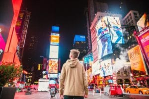 Blue Digital Header image of a young boy looking into a time square at night time with all the neon advertising
